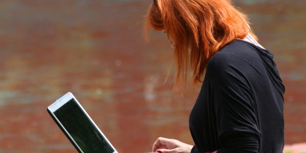 Woman with red hair sitting on step, typing on laptop